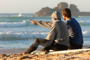 two-surfers-talking-beach-16421128