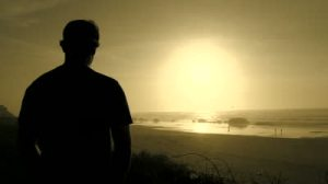 stock-footage-silhouette-of-man-standing-on-beach-watching-sunset-over-pacific-ocean